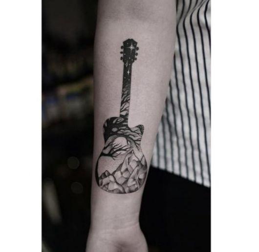 Silhueta de um violão e seu interior é preenchido com a paisagem de uma floresta, onde há árvores, montanhas e a lua.