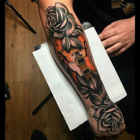 Tatuagem na parte externa do antebraço com o corpo de uma guitarra e flores ao seu redor.