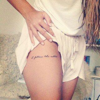 Menina com frase tatuada na coxa.