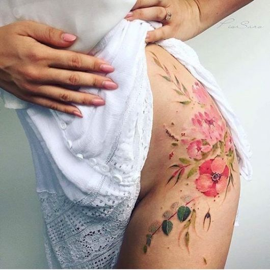 Tatuagem colorida com flores e folhas.