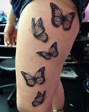 Tatuagem com cinco borboletas na coxa.