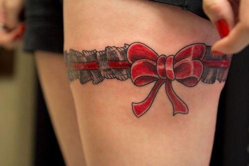 Tatuagem de cinta liga preta e vermelha.