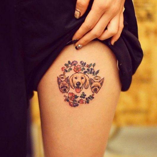 Tatuagem com um círculo de flores e três cachorros dentro.