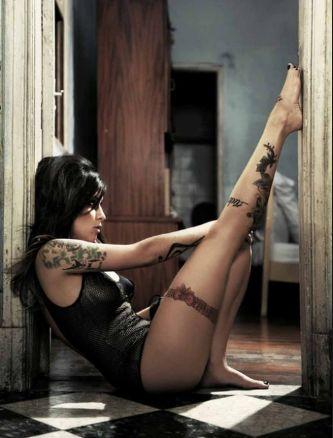 Pitty sentada no chão, mostrando todas suas tatuagens.