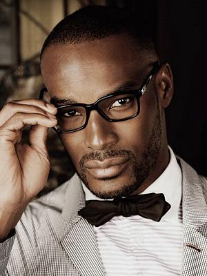 Homem com trajes sociais e gravata borboleta usando um óculos quadrado masculino de grau de hastes pretas.