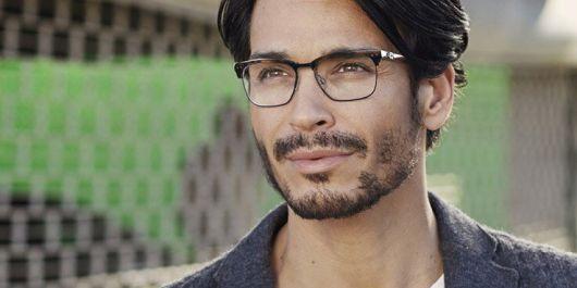 Homem de cabelos longos jogados para o lado olhando para o horizonte. Ele usa um óculos com a haste superior mais grossa que as outras partes.