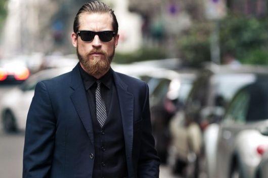 Homem de terno e gravata escuros usando um óculos quadrado masculino de sol com lentes pretas.