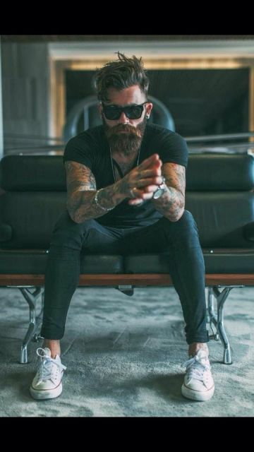 Homem tatuado com trajes simples e escuros sentado em um sofá. Ele usa um óculos quadrado grande com lentes e hastes escuras.