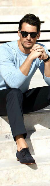 Homem vestido com estilo casual sentado em uma escada usando um óculos quadrado masculino de sol.
