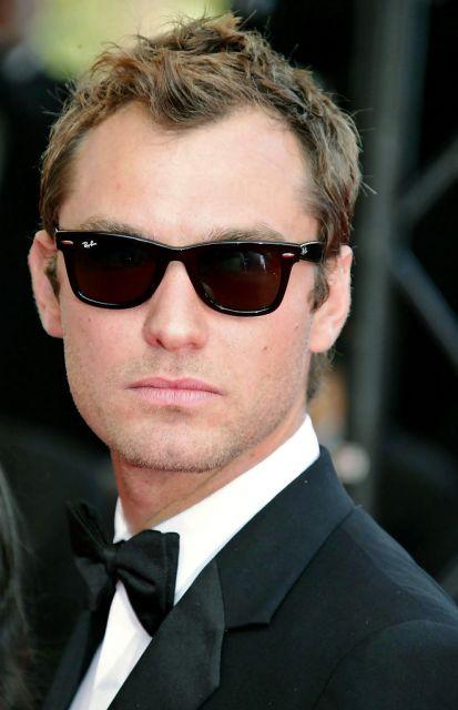 O ator Jude Law vestindo um traje característico das premiações de cinema acompanhado de um óculos quadrado masculino da Ray-Ban.