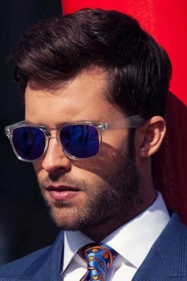 Homem de terno e gravata usando um óculos quadrado masculino de sol com hastes transparentes e lente espelhada.