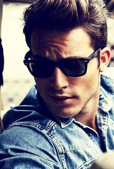Homem com uma jaqueta jeans olhando para o lado. Ele usa um óculos quadrado masculino de sol com hastes grossas e lentes escuras.