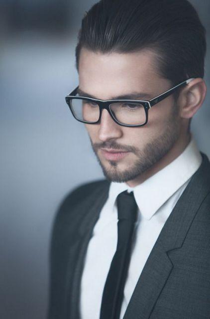 Homem de terno, gravata e cabelo penteado para trás usando um óculos quadrado de grau com hastes pretas e pequenos detalhes em branco.