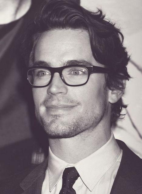 Homem de cabelo grande jogado para trás usando um óculos quadrado de grau com as pontas levemente arredondadas,