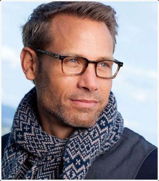 Homem de cachecol olhando para o lado usando um óculos quadrado de grau com as hastes levemente detalhadas.