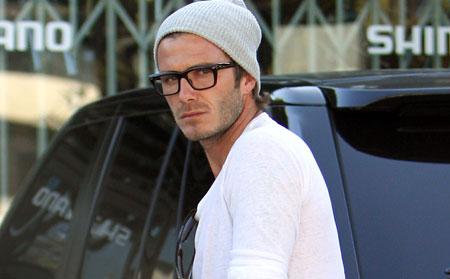 O jogador David Beckham usnado uma camiseta simples branca e um capuz acompanhado de um óculos quadrado de grau com hastes pretas bem definidas.