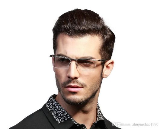 Homem de camisa social e cabelo penteado usando um óculos de grau quadrado discreto com hastes transparentes.