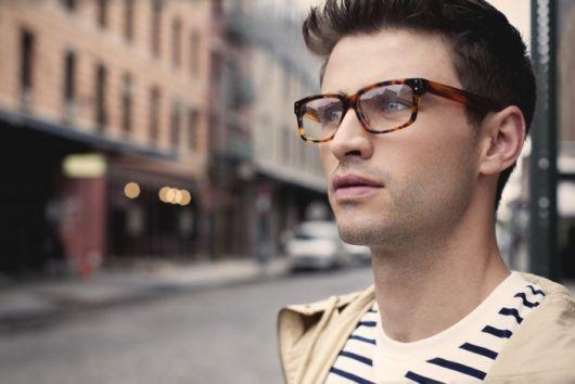 Foto de um homem na rua em primeiro plano com o fundo desfocado. Ele usa um óculos quadrado de grau cujas hastes misturam diferentes tipos de cor.