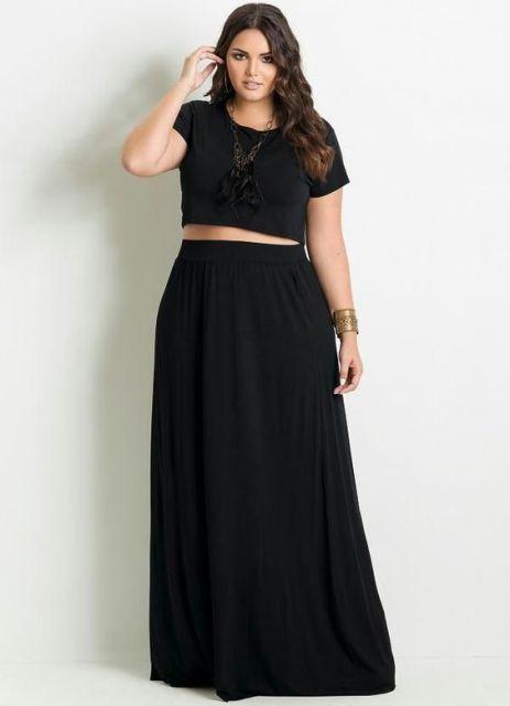 Modelo usa saia preta longa e blusa preta cropped na mesma cor.
