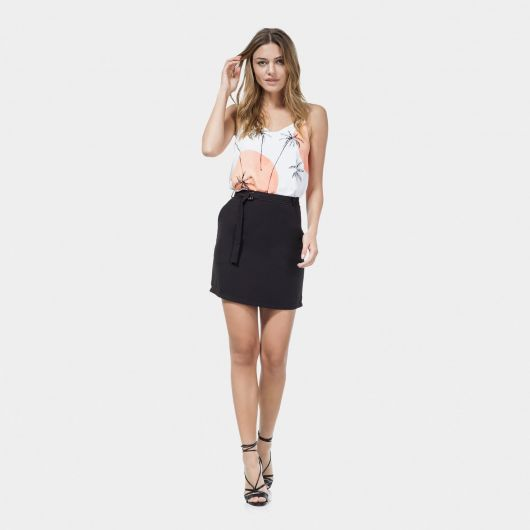 Modelo usa saia preta, blusa estampada e sandalia de salto na cor preta.