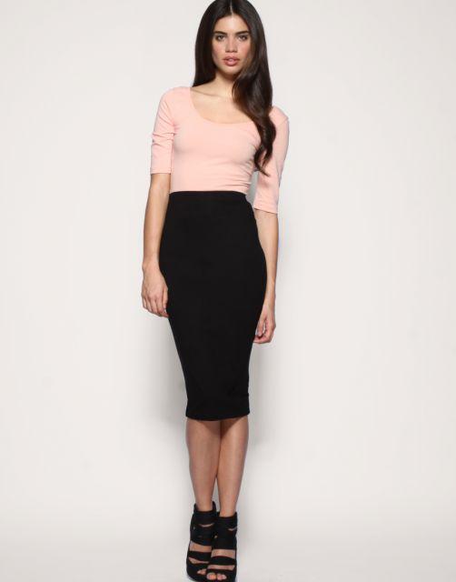Modelo usa saia preta midi justa, blusa rosa clarinho meia manga e sapato preto com salto alto.