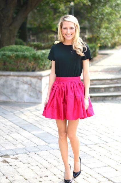 Modelo usa saia rosa, blusa e sapato preto.