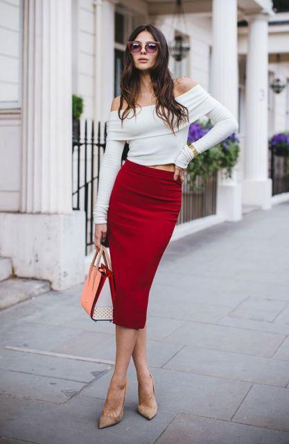 Modelo usa saia vermelha, blusa branca manga longa ombro a ombro com sapato nude.