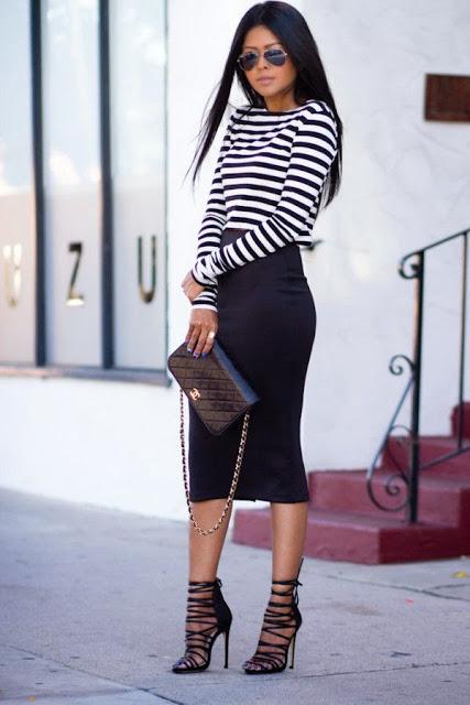 Modelo usa saia preta, blusa listrada preta e branca e sandalia preta.