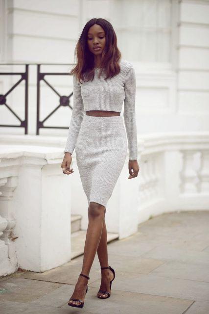 Modelo usa saia justa midi cinza e blusa cinza na mesma cor.