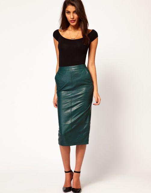 Modelo usa saia verde de couro, blusa preta e sapato preto.