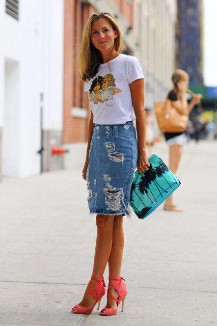 Modelo usa saia jeans destruída, blusa manga curta estampada, sandalia laranja e bolsa de mao verde agua com preto.