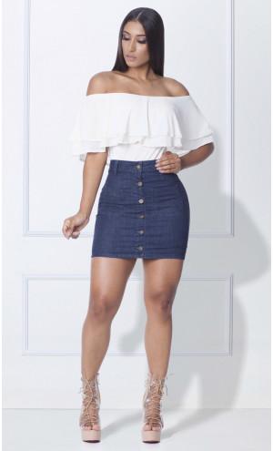 Modelo usa saia jeans de botoes, blusa branca ombro a ombro e sandalia nude.