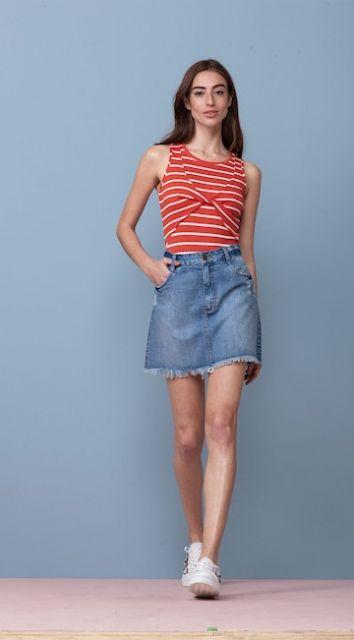 Modelo usa saia jeans, blusa listrada vermelho com branco e tenis branco.