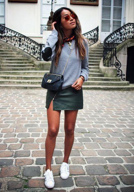 Modelo usa saia verde curta com fenda de couro, blusa cinza, tenis branco e bolsa.