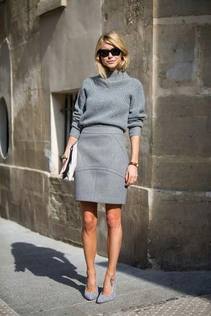 Modelo usa saia e blusa cinza e sandalia.