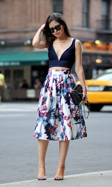 Modelo usa saia midi estampada rodada, blusa cropped decotada e sapato nude.