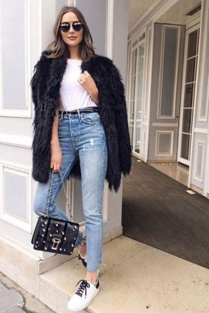 Modelo usa calça jeans azul, bolsa preta, casaco preto.