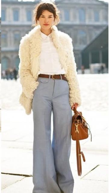 Modelo usa calça cinza pantalona, blusa branca, casaco amarelinho e bolsa marrom.