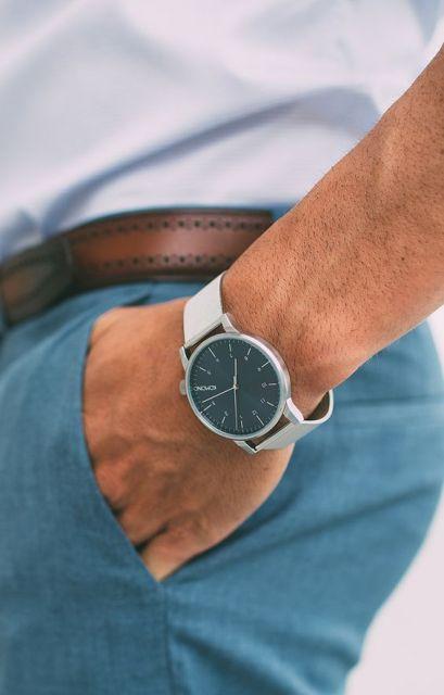 Foto do pulso de um homem com a mão no bolso. Ele usa um relógio prata arredondado sem muitos detalhes, apenas ponteiros e os números que indicam as horas.