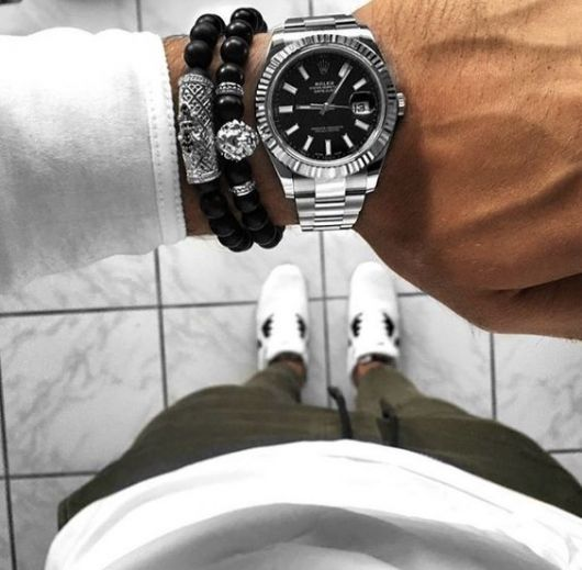 Foto do pulso de um homem com trajes casuais com foco no relógio bem elaborado acompanhado de duas pulseiras.