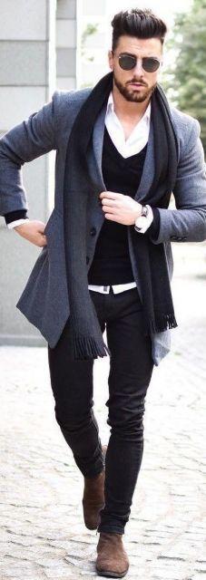 Foto de um homem caminhando na rua com um blazer, calça apertada, cachecol, óculos escuros e um relógios prata.