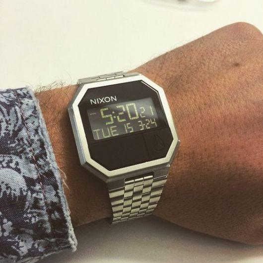 Relógio prata da Nixon quadrangular no pulso de um homem. As horas são apresentados por numerais acompanhados da data.