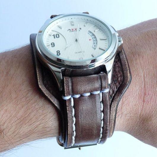 Foto de um relógio com aro prata arredondado e uma pulseira grossa de couro.