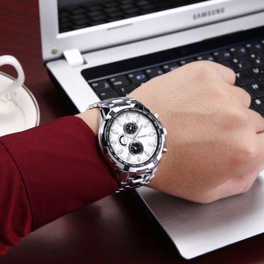 Foto do pulso de um homem posicionado em frente a um notebook. O relógio conta com diversos detalhes e funcionalidades, além de um design ousado e chamativo.