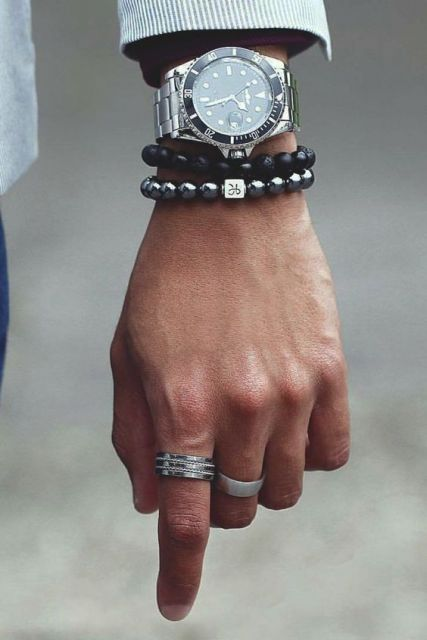 Foto do pulso de um homem usando duas pulseiras e dois anéis. Acima das pulseiras está um relógio prata muito detalhado no aro e na pulseira.