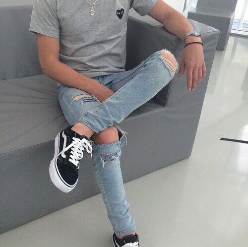 Foto do corpo de um homem sentado em um sofá. Ele usa um tênis da Vans, calça jeans rasgada e camiseta lisa. No seu braço que está recostado na lateral do sofá, dá para perceber um relógio prata arredondado.