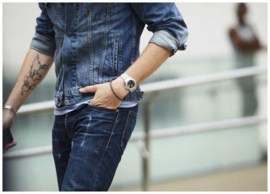 Foto do corpo de um homem caminhando na rua vestindo jaqueta e calça jeans. Em um de seus pulsos está um relógio prata em formato arredondado.