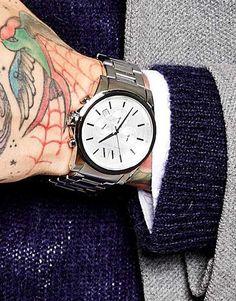 Foto do pulso e parte da mão de um homem vestindo roupas de frio. Acima de sua mão tatuado está um relógio prata chique com ponteiros minimalistas.