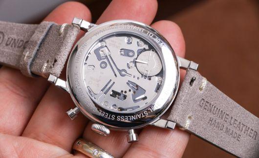 Foto de um relógio na palma da mão de uma pessoa. O aro e interior do relógio contam com diversos detalhes e são feitos em prata, enquanto as pulseiras são feitas de couro.