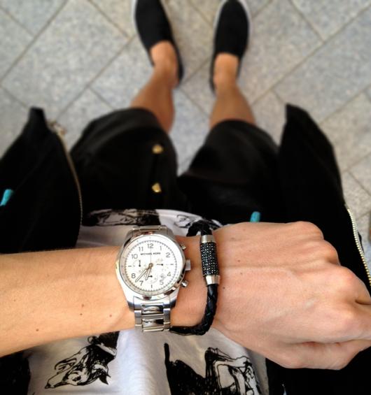 Foto do pulso de um homem que usa um relógio prata arredondado acompanhado de uma pulseira.